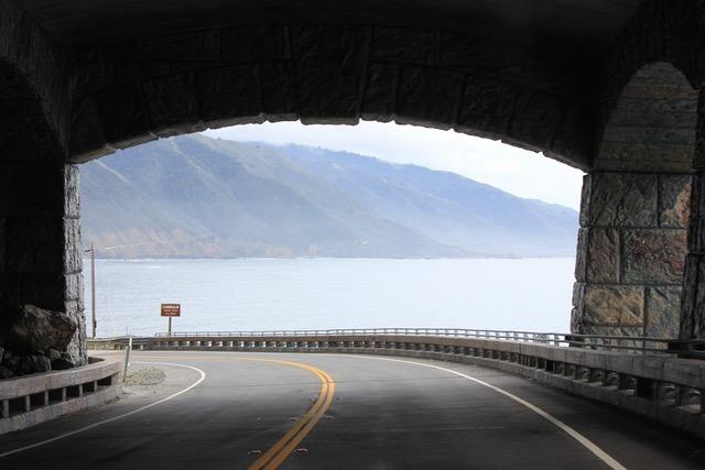 Road through dark tunnel with sea, mountains beyond tunnel